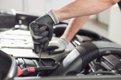 Kantjusterad bild av bilmekanikern som reparerar bilen i billager Royaltyfria Bilder