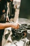 Kantjusterad bild av bilmekanikern som reparerar motorcykeln Royaltyfria Bilder