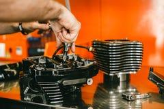 Kantjusterad bild av bilmekanikern som reparerar motorcykeln Fotografering för Bildbyråer