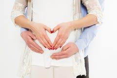 Kantjusterad bild av den härliga gravida kvinnan och hennes stiliga maken som kramar magen älska tecknet Lycklig händelse, födels fotografering för bildbyråer