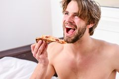 Kantjusterad bild av den shirtless sexiga mannen med pizza p? s?ng Man den sk?ggiga stiliga grabben som ?ter ostliknande mat f?r  royaltyfri foto