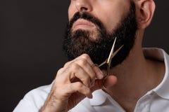 Kantjusterad bild av den skäggiga mannen med scissord över mörk bakgrund fotografering för bildbyråer
