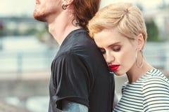 kantjusterad bild av den stilfulla flickvännen som kramar den tatuerade pojkvännen royaltyfria bilder