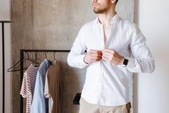 Kantjusterad bild av en man i den vita skjortan som knäppas upp Arkivfoto