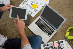Kantjusterad bild av formgivaren som använder den digitala minnestavlan, medan sitta på golv Arkivbilder