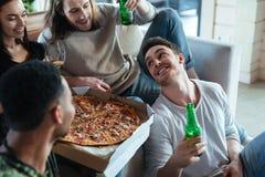 Kantjusterad bild av fyra vänner som sitter med pizza Fotografering för Bildbyråer