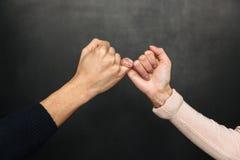 Kantjusterad bild av hållande lillfingrar för asiatiska par till varandra Arkivbilder
