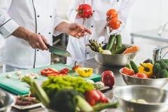 kantjusterad bild av kockar som förbereder grönsaker royaltyfri bild