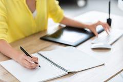 kantjusterad bild av kvinnlig freelancerhandstil i lärobok och arbete på datoren royaltyfri foto