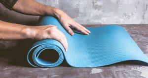 Kantjusterad bild av manhänder som rullar matt yoga royaltyfri fotografi