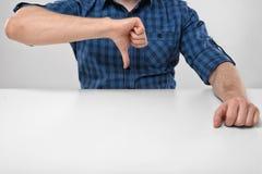 Kantjusterad bild av manliga händer som ner visar tummar den dåliga falska gesthanden betyder nr Royaltyfri Foto