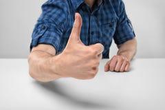 Kantjusterad bild av manliga händer som visar upp tummar Arkivfoto