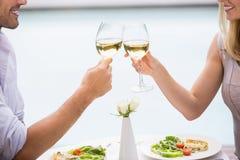 Kantjusterad bild av par som rostar vitt vin Arkivbilder