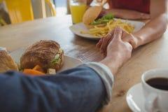 Kantjusterad bild av parinnehavhänder i kafé fotografering för bildbyråer