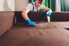 Kantjusterad bild svampar f?r flytande f?r cleaningbegreppsdishwashing Manlig hand i skyddande handskar som g?r ren soffasoffan i royaltyfri foto