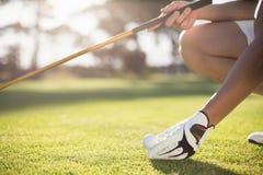Kantjusterad golfareman som förlägger golfboll på utslagsplats royaltyfri bild