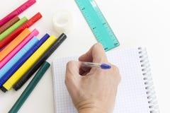 Kantjusterad handhandstil i anteckningsbok Mångfärgade markörpennor, anteckningsbok, linjal på vit Kontors- och skolateckning arkivbilder