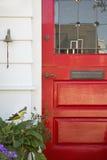 Kantjusterad röd ytterdörr av ett hem Arkivbilder