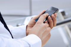 Kantjusterad sikt av affärsmannen som rymmer mobiltelefonen Arkivfoton