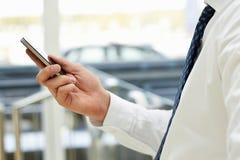 Kantjusterad sikt av affärsmannen som rymmer telefonen som framme står Royaltyfri Bild