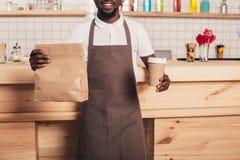 kantjusterad sikt av afrikansk amerikanbaristaen som rymmer den disponibla koppen kaffe och den kraft packen royaltyfri foto