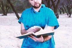 kantjusterad sikt av den koncentrerade stiliga skäggiga mannen i blått kimonosammanträde som bläddrar igenom den stora boken arkivfoto