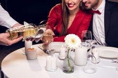 kantjusterad sikt av hällande vin för uppassare medan par som har det romantiska datumet royaltyfri fotografi