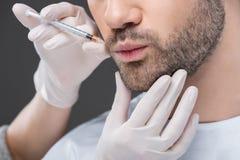 kantjusterad sikt av händer i medicinska handskar som gör skönhetinjektionen för man, royaltyfria bilder