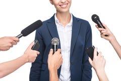 kantjusterad sikt av journalister med mikrofoner som intervjuar le affärskvinnan, Royaltyfri Fotografi