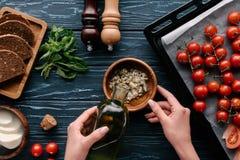 Kantjusterad sikt av kvinnliga händer som tillfogar olja till vitlök på den mörka trätabellen med tomater arkivbild