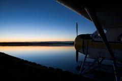 kantjusterad sikt för solnedgång för lakeseaplanesida Arkivbild