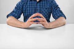 Kantjusterad stående av ett mansammanträde med hans knäppte fast fingrar Royaltyfri Fotografi