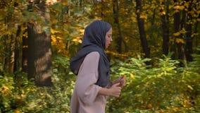Kantjusterad stående i profil, docka som skjutas av ung muslimsk flicka i hijab som kör i höstlig skog lager videofilmer