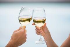 Kantjusterade händer av par som rostar vitt vin Arkivbilder