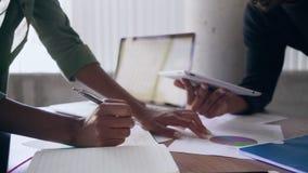 Kantjusterade händer av undersökande data för affärsfolk på tabellen på kontoret lager videofilmer