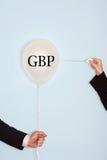 Kantjusterade händer som rymmer visaren och poppar ballongen med text som säger GBP Royaltyfri Bild