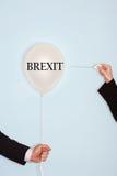Kantjusterade händer som rymmer visaren och poppar ballongen mot ljus - blå bakgrund med text som säger Brexit Arkivfoto