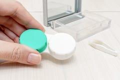 Kantjusterade kvinnliga händer som rymmer en behållare för kontaktlinser arkivbilder