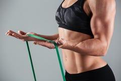 Kantjusterat foto av den musculary kvinnan som övar med motståndsmusikbandet arkivfoto