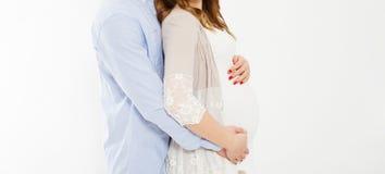 Kantjusterat foto av det gladlynta anseendet för ung man med hans gravid kvinna som isoleras över den vita bakgrundsväggen royaltyfria foton