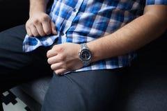 Kantjusterat foto av en stark man i en blå rutig skjorta med korta muffar, mörk jeans i timmar på hans handled som sitter arkivbilder