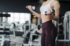 Kantjusterat kroppslut upp av den unga attraktiva kvinnan i sportkl?der som rymmer vikthanteln som g?r konditiongenomk?rare i idr arkivbilder