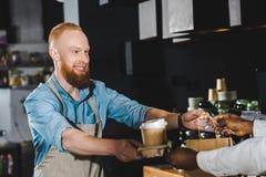 kantjusterat skott av att le den skäggiga unga baristaen som ger den pappers- påsen och disponibla kaffekoppar till afrikansk ame fotografering för bildbyråer