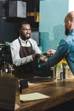 kantjusterat skott av den gladlynta afrikansk amerikanbaristaen som ger koppen kaffe till den skäggiga unga klienten arkivbild