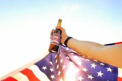 Kantjusterat skott av den hållande ölflaskan för manlig hand & nationsflaggan av USA mot inställningssolen Flodbakgrund lycklig s Royaltyfri Foto