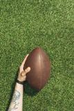 kantjusterat skott av den hållande rugbybollen för man i hand på gräsplan royaltyfria bilder