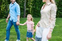 kantjusterat skott av den lyckliga familjen som rymmer händer och tillsammans går arkivfoton