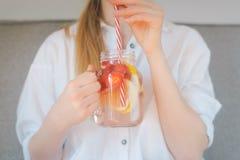 Kantjusterat skott av den unga kvinnan som dricker hem gjord ny sommardrin Arkivbilder