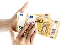 Kantjusterat skott av en oigenkännlig sedel för euro för kvinnahandinnehav arkivfoto