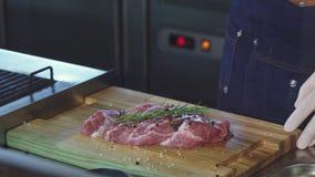Kantjusterat skott av en yrkesmässig kock som tillfogar olivolja som förbereder grisköttkött arkivfilmer